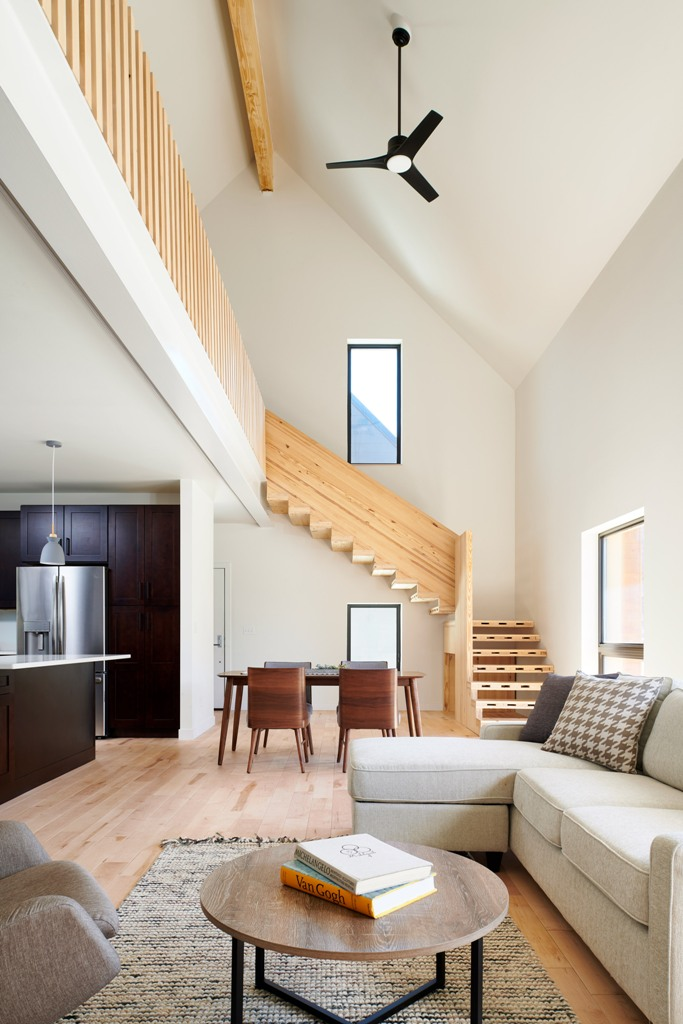 The main space is an open layout with a kitchen, dining space and living room plus a large wooden staircase that leads to the second floor