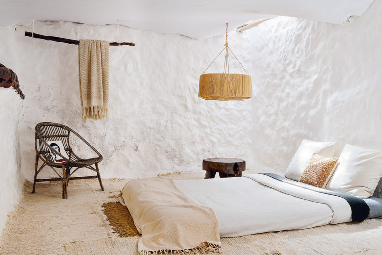 The master bedroom shows off layered rugs, a mattress, a wicker chair, a wooden stool, a wicker lamp and a lanket hanging on a branch