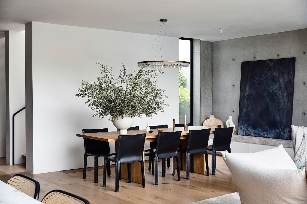 The formal dining space is done with a wooden table and black leather chairs plus a crystal chandelier