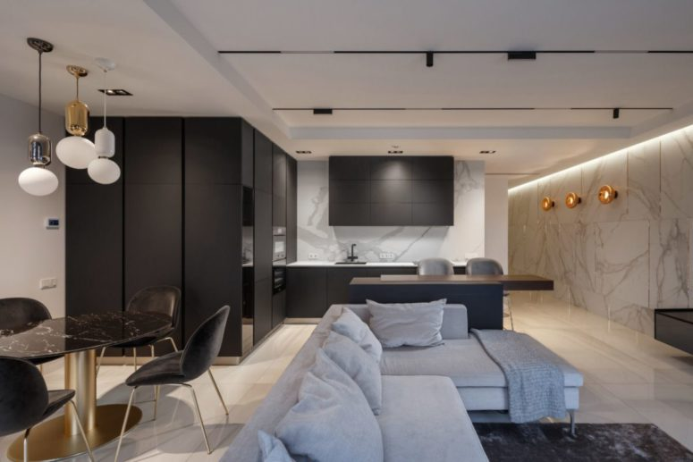 The kitchen is sleek and black, with a marble wall, and the dining space is done with a black marble table to echo with it