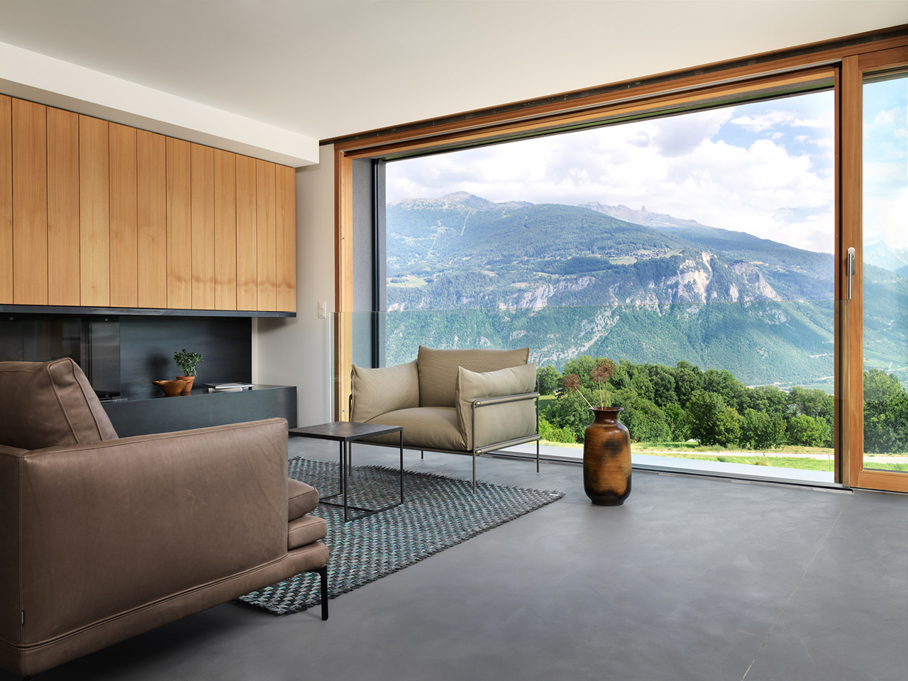 The living room shows off amazing views of the slopes, it's done with sleek black surfaces and wood, the furniture is contemporary