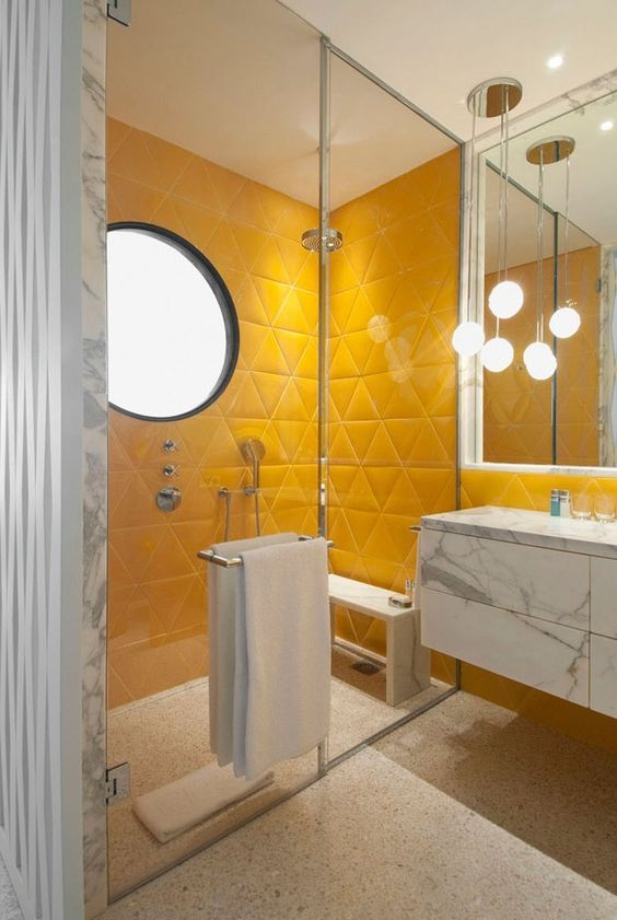 a bright bathroom in sunny yellow, with a marble floating vanity, a terrazzo floor and cool pendant lamps