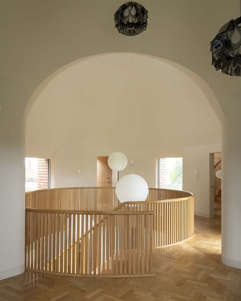 On the first floor, a double height living room is framed by the arched geometry of the intersection of two cones