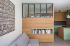 04 The living room consists of a grey sofa, a large storage unit that doubles as a space divider