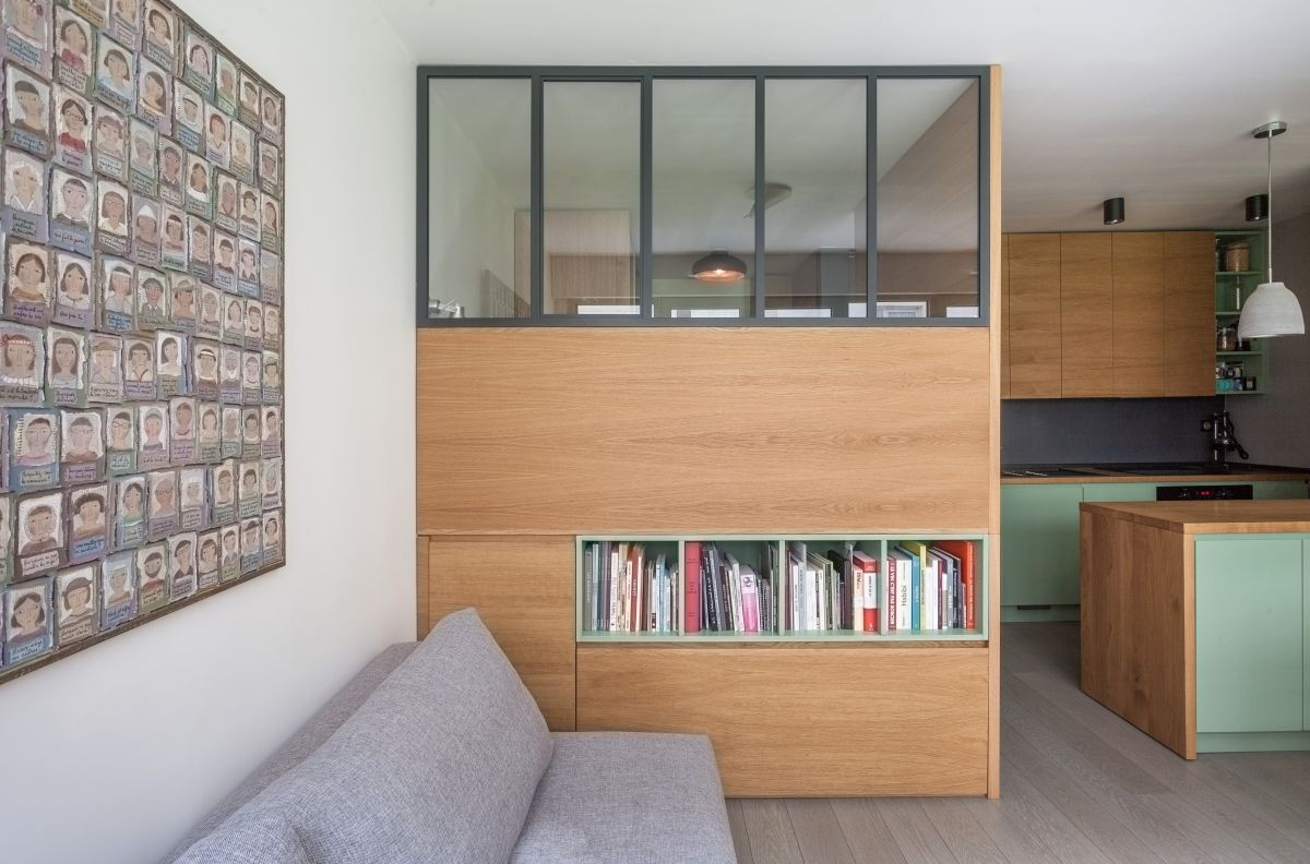The living room consists of a grey sofa, a large storage unit that doubles as a space divider