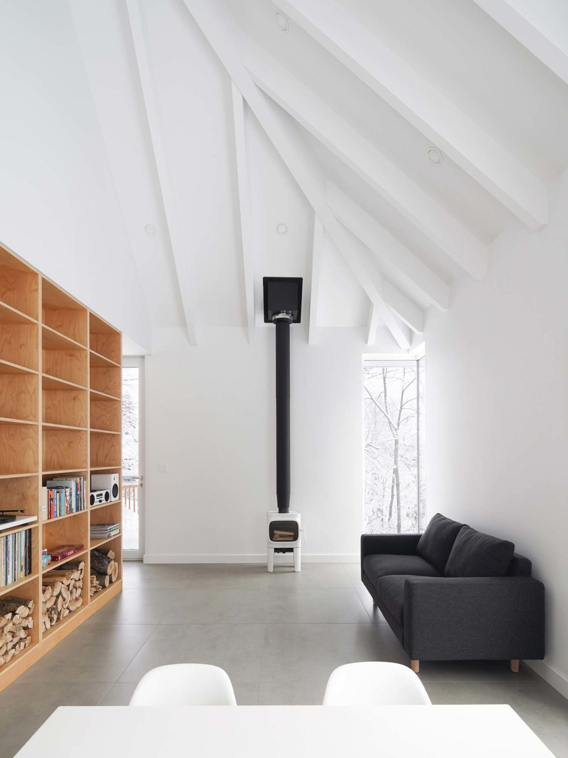 The living room is done with a grey sofa, a small fireplace and a large plywood storage units that doubles as a space divider