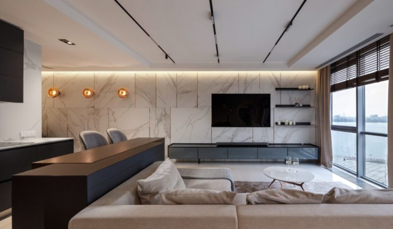 The living room is done with comfortable modern furniture, white marble on the wall and a dark TV unit