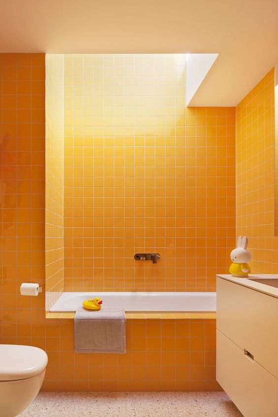 a bright bathroom done in sunny yellow, with touches of white and a skylight to create a mood