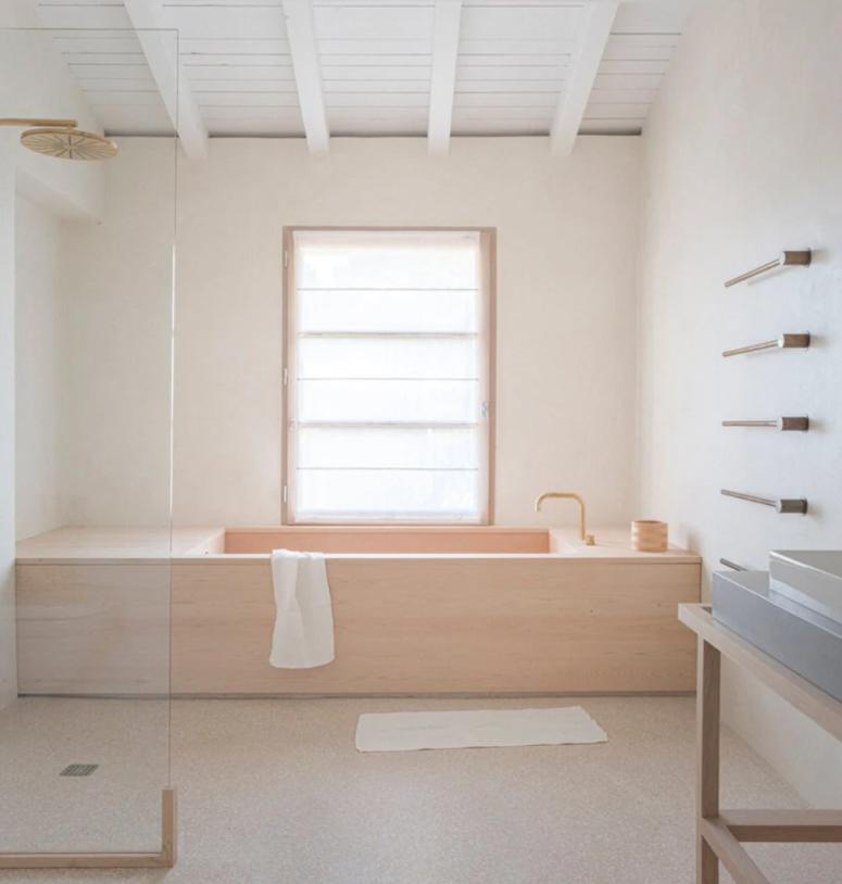 a minimalist bathroom with white walls and wood clad tub