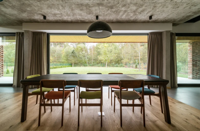The dining space is placed in front of the window, with colorful chairs and a concrete ceiling that contrasts the warm decor