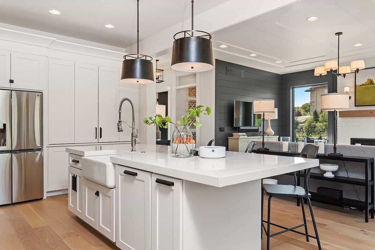 The kitchen is adjusted to the living room and is done in white, with blakc lamps