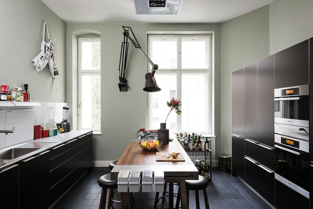 The kitchen is done with black sleek cabinets, with a statement wall lamp and a cool dining table