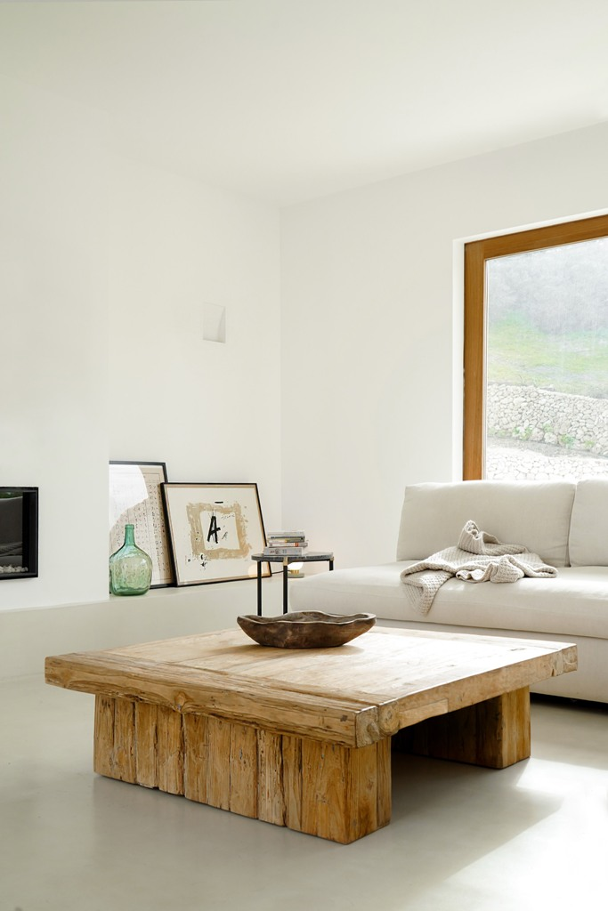 The living room features a wooden table, some artworks and a comfy sofa and cool views