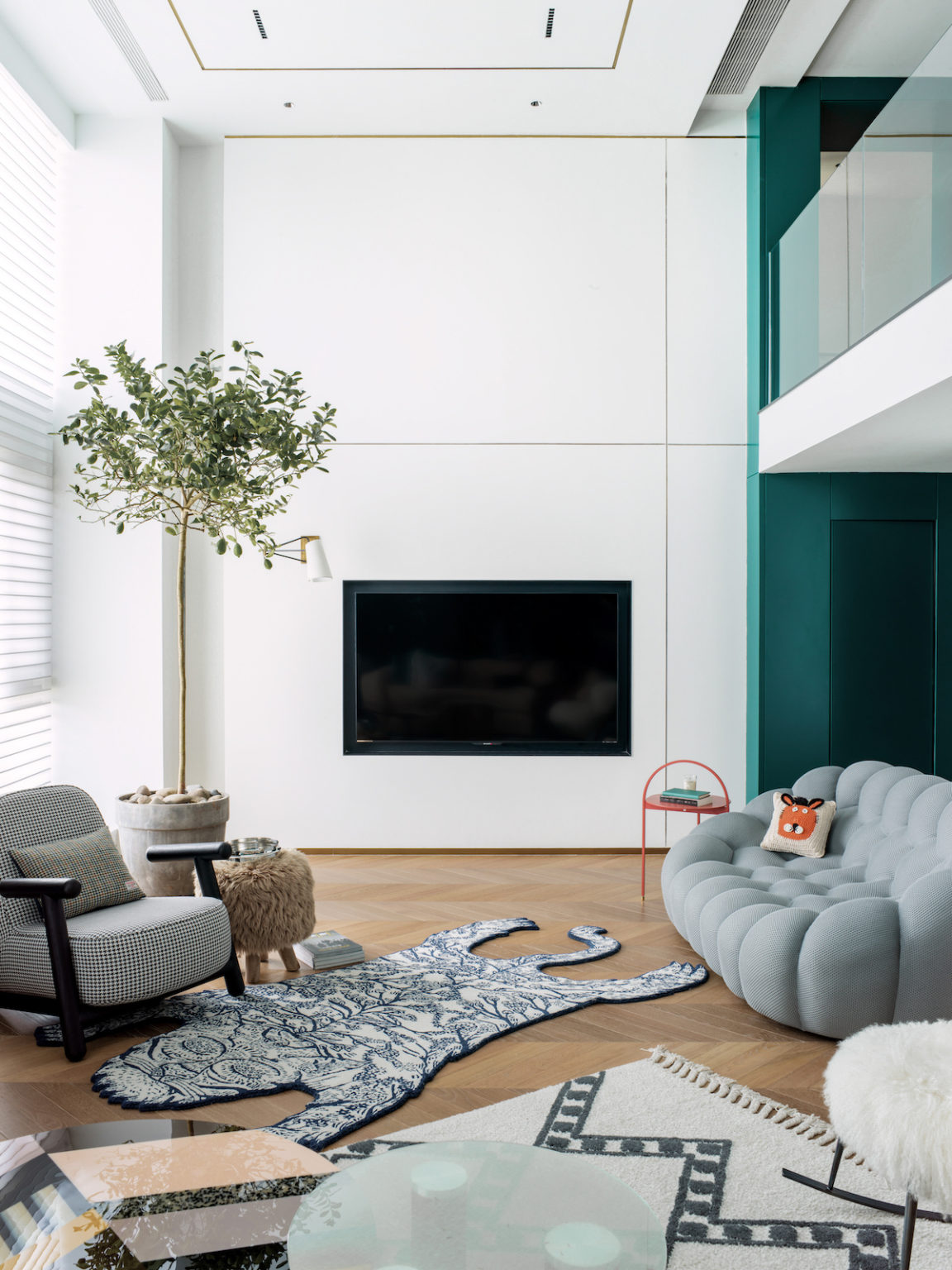 This is another sittign room, with a catchy soft sofa, a built in TV, layered rugs and a potted tree