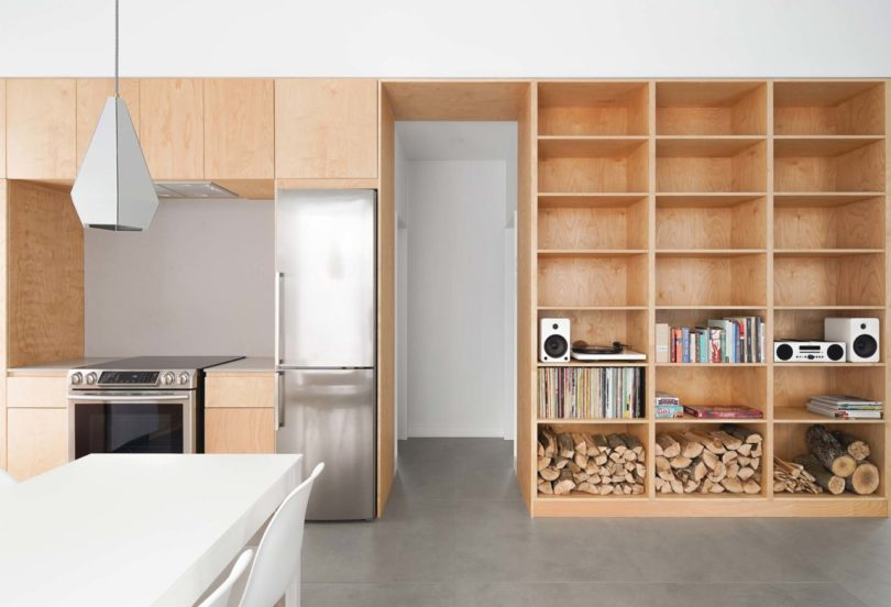 This storage unit continues to the kitchen and features sleek kitchen cabinets and built in appliances
