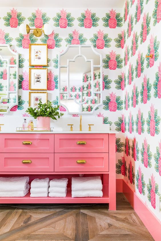 the whimsical pineapple wallpaper and bright pink color scheme in this bathroom screams Palm Beach