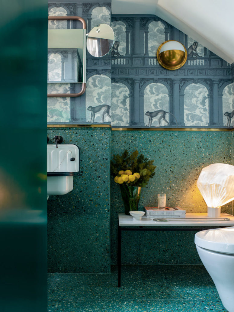 The bathroom continues with the colors of the apartment - teal and deep green and surprises with catchy wallpaper