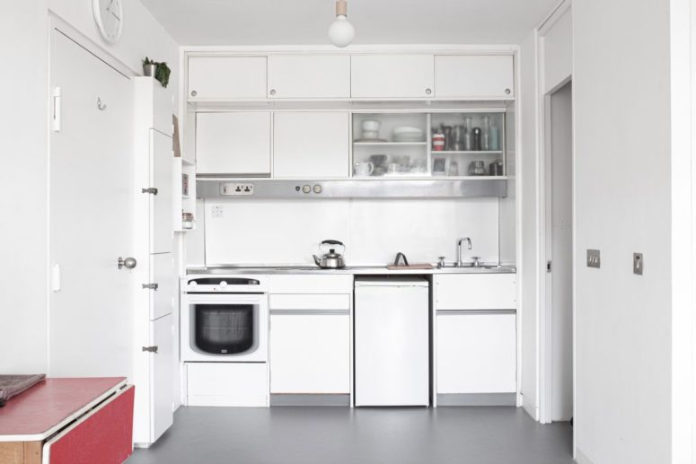 The kitchen is very compact and white, which helps to give it a bright and airy look