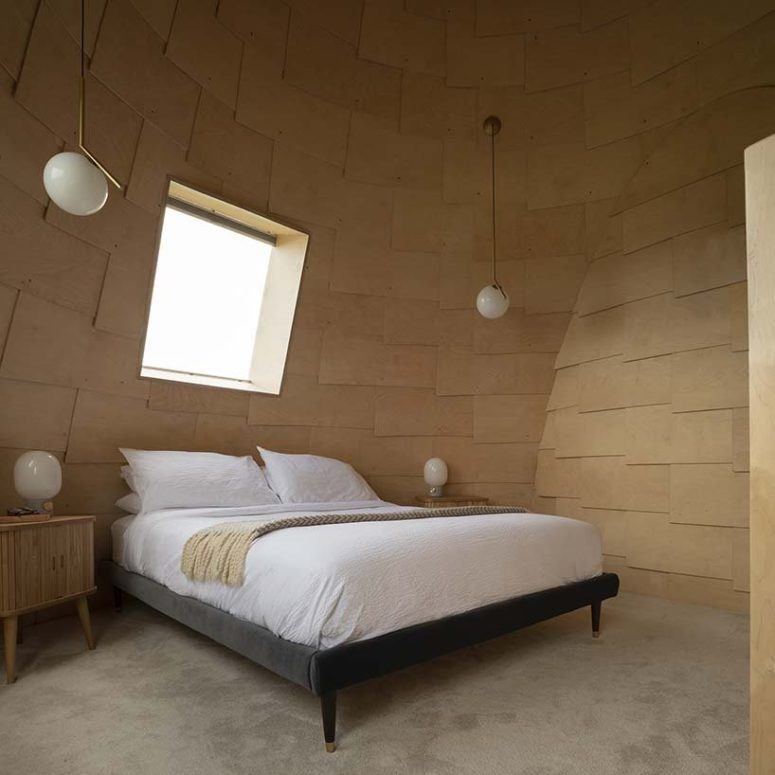 The master bedroom is also covered with bent plywood and the furniture is simple