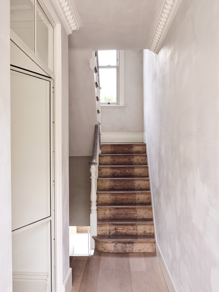 The staircase is dark stained to make a contrast to the white walls and add texture
