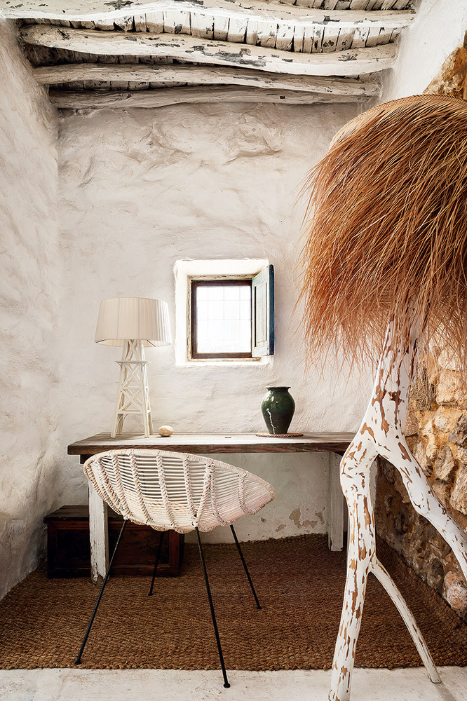 The tiny home office is done with a shabby chic desk, a wooden box, a jute rug, some catchy decor and a green vase