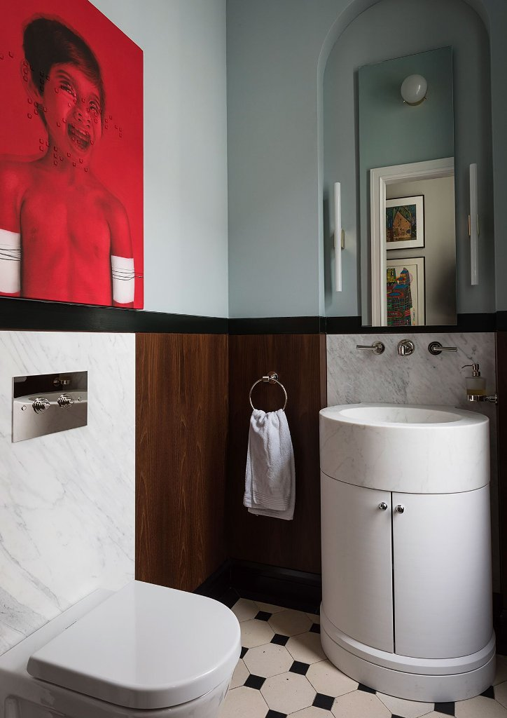 The bathroom is overwhelmed with a statement artwork in red