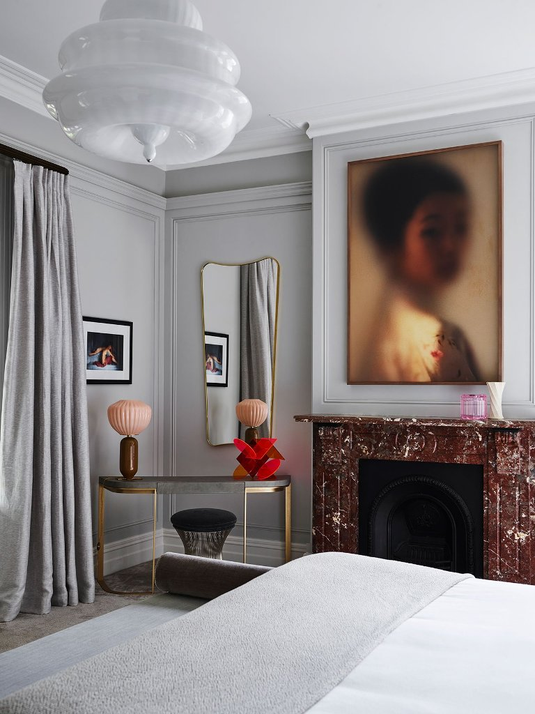 The bedroom can boast of a lovely stone clad fireplace and a muted artwork