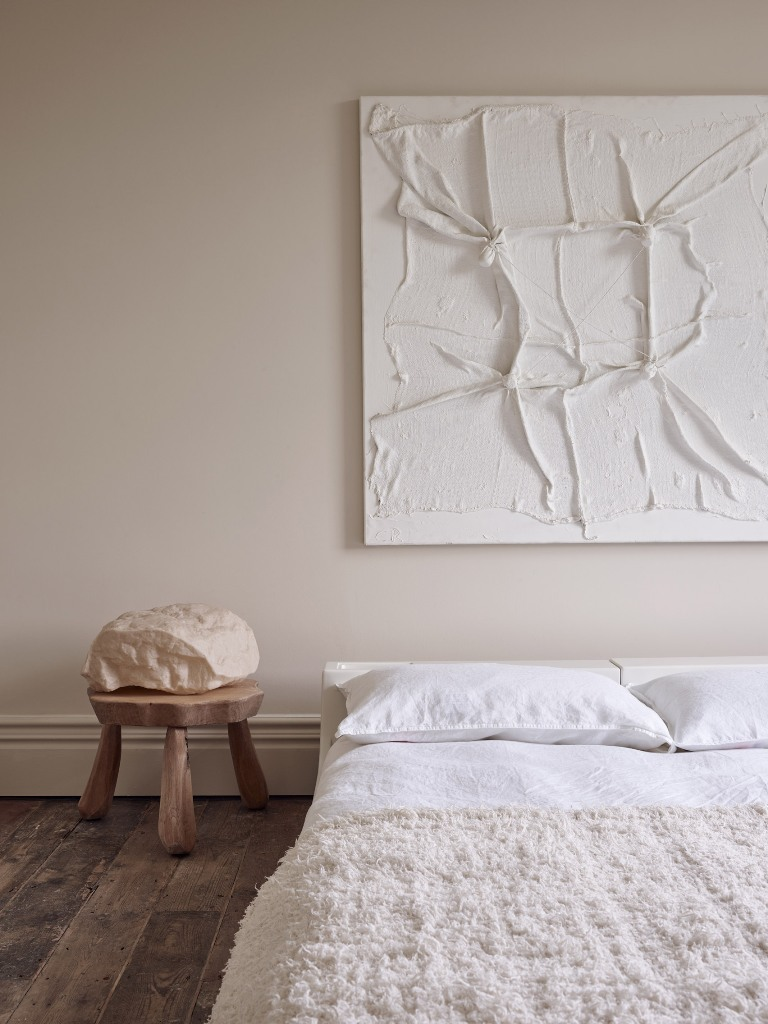 The bedroom is done with neutral walls, simple furniture and a very catchy piece of art