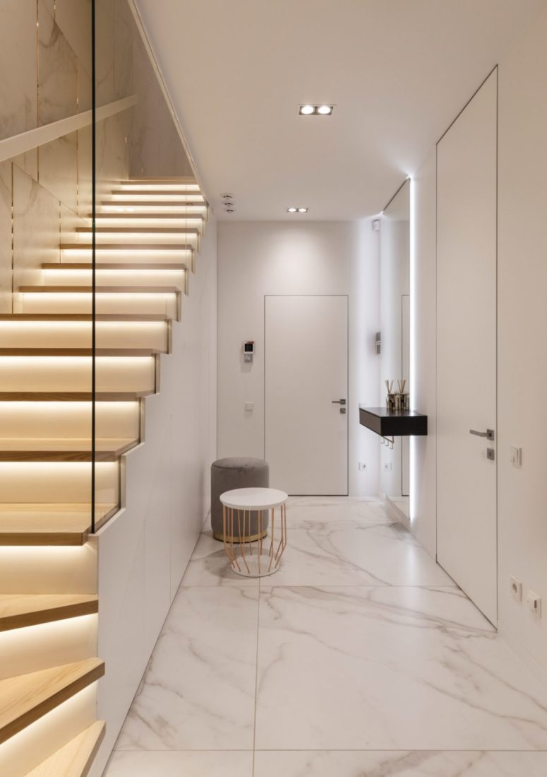 The entryway is very laconic, with white marble tiles and neutral stools and tables