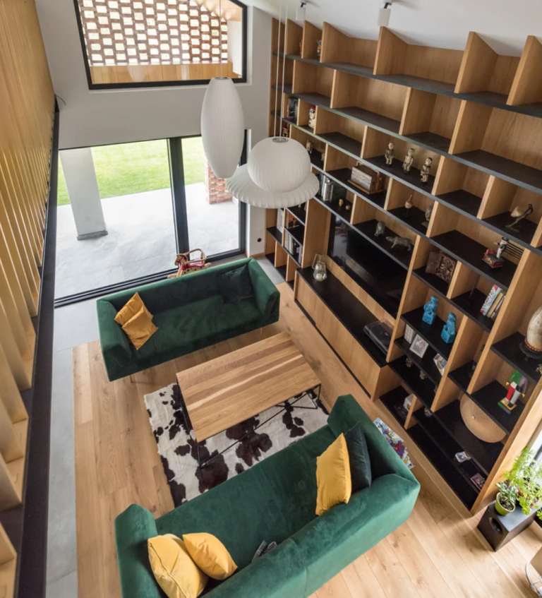 The living room is done with bold green sofas, yellow pillows, a large bookcase that takes a whole wall