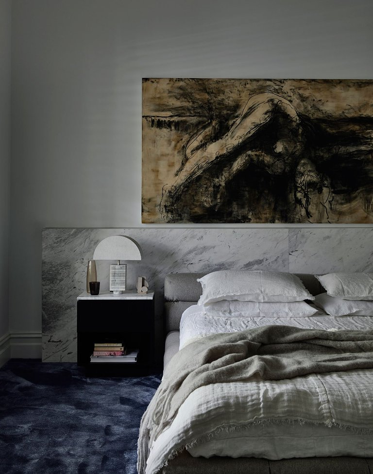 The master bedroom is done with stone, a catchy artwork and a brushstroke rug