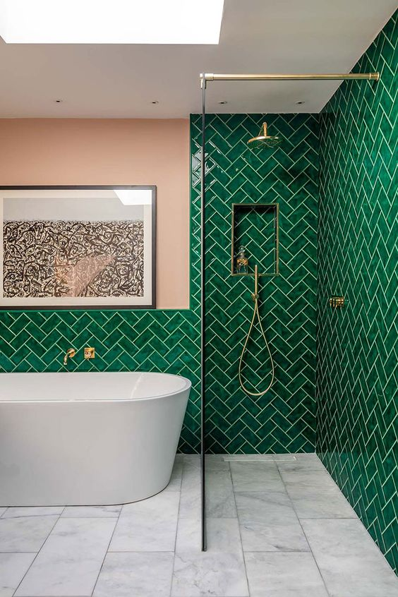 bright emerald tiles clad in a herringbone pattern, with a pink wall and touches of gold