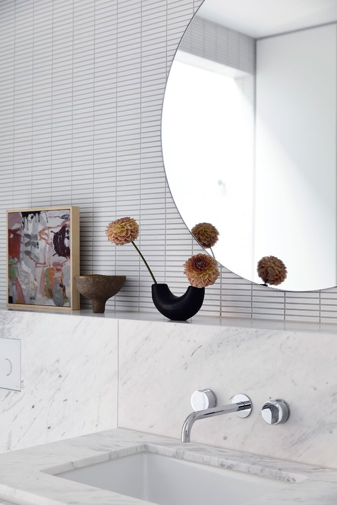 The bathroom is contemporary and neutral, done with large stone tiles and some usual smaller ones