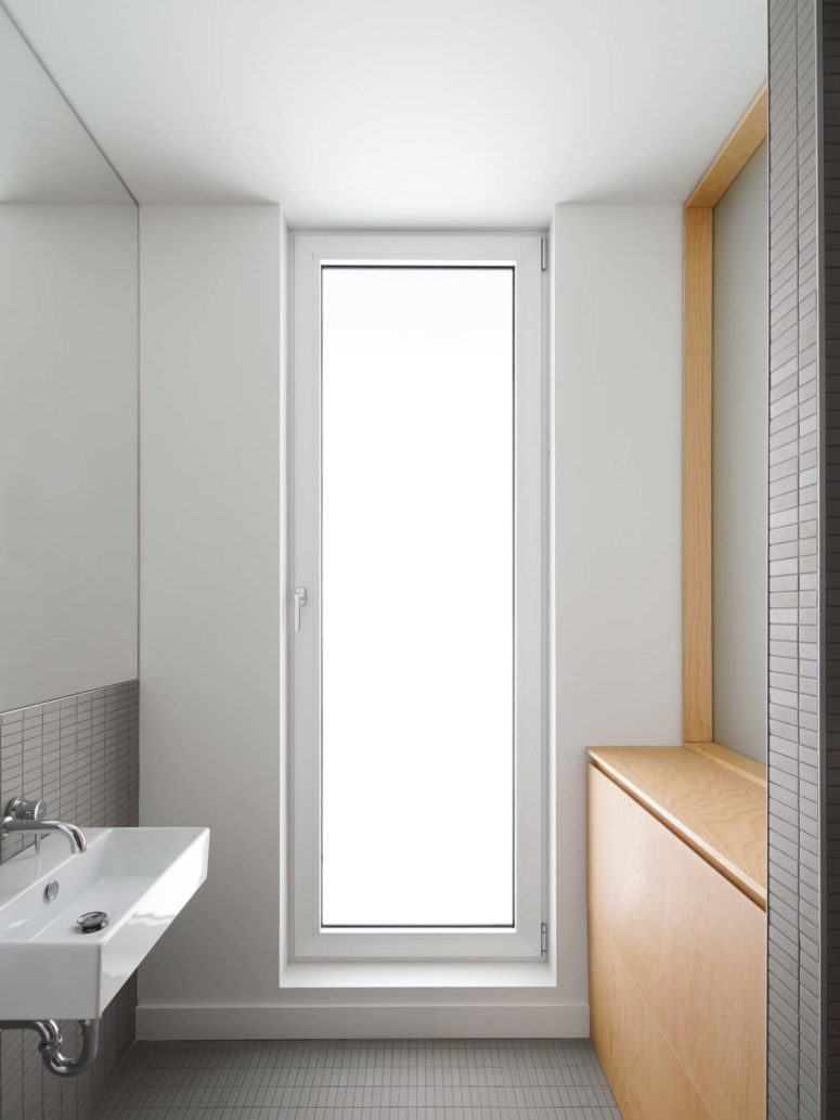 The bathroom is small, there's a frosted glass door, sleek plywood items and grey tiles on the walls and floor