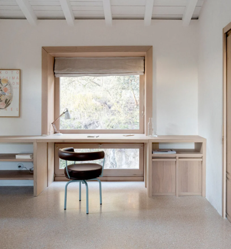 The home office continues the kitchen style, with a plywood desk, storage and a window frame plus a leather chair