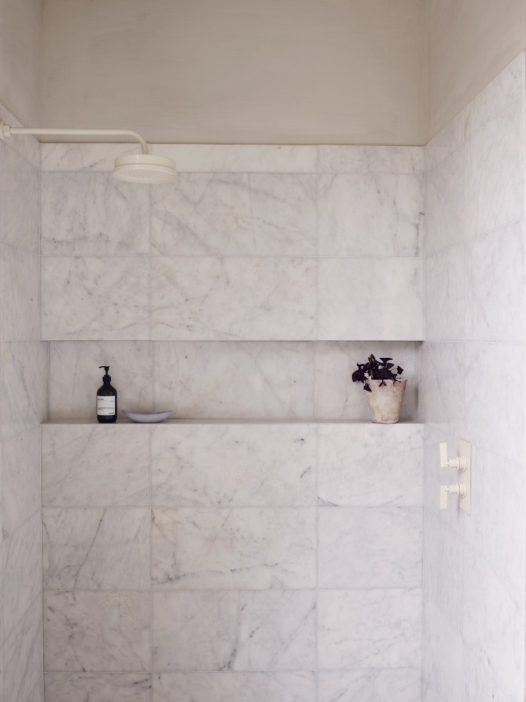 The small bathroom features a shower space clad with white marble tiles