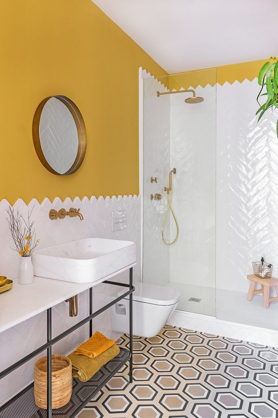 a colorful bathroom with mustard walls, a mosaic floor, mustard textiles and brass fixtures to raise your mood