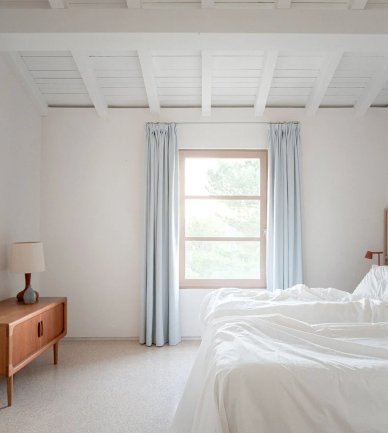 The bedroom is very airy, with a mid-century modern sideboard, a bed, sconces and blue curtains