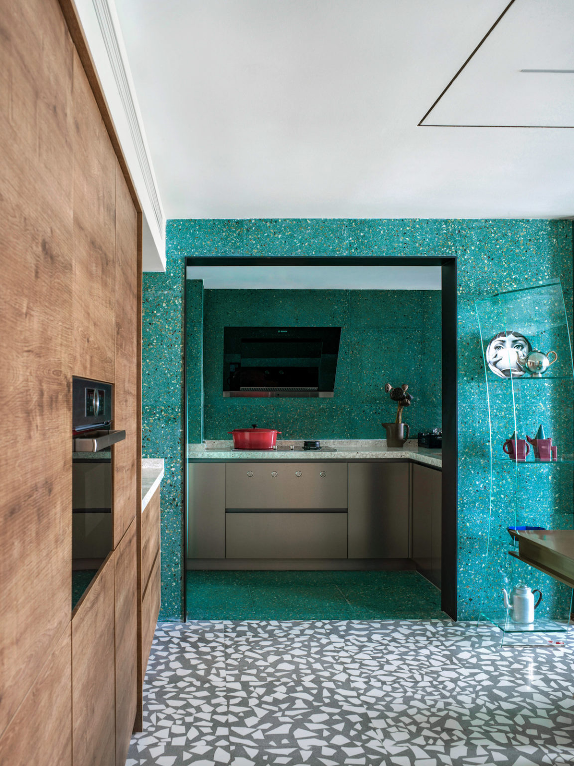 The cooking zone is pretty small, with a TV and simple grey cabinets with terrazzo countertops