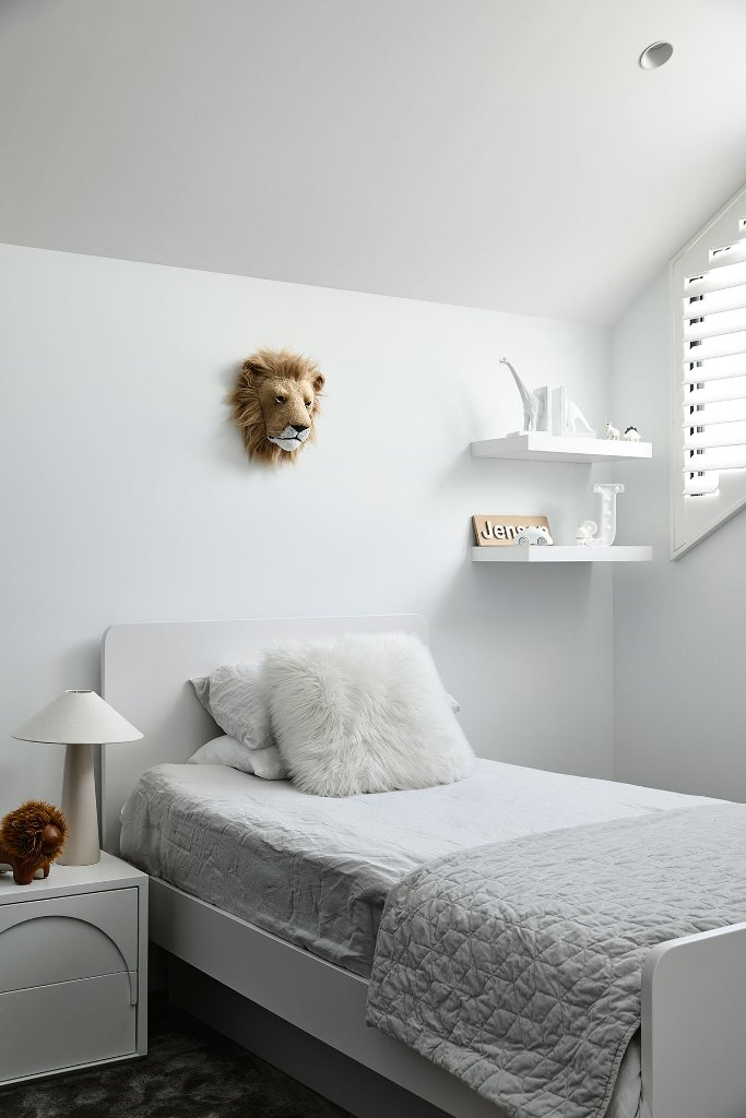 The kid's room is all white and off white, with some furniture and a touch of fun