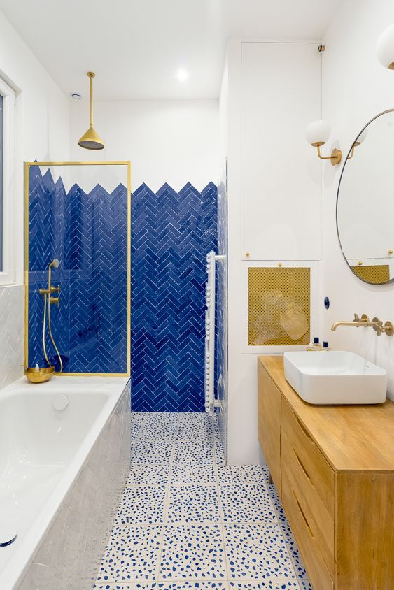 a bold bathroom with electric blue tiles, a dolmatin tile floor, a bold wooden vanity and a matching cover plus touches of gold
