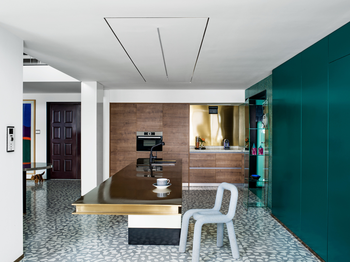There are also wooden cabinets with built in appliances and a polished gold backsplash
