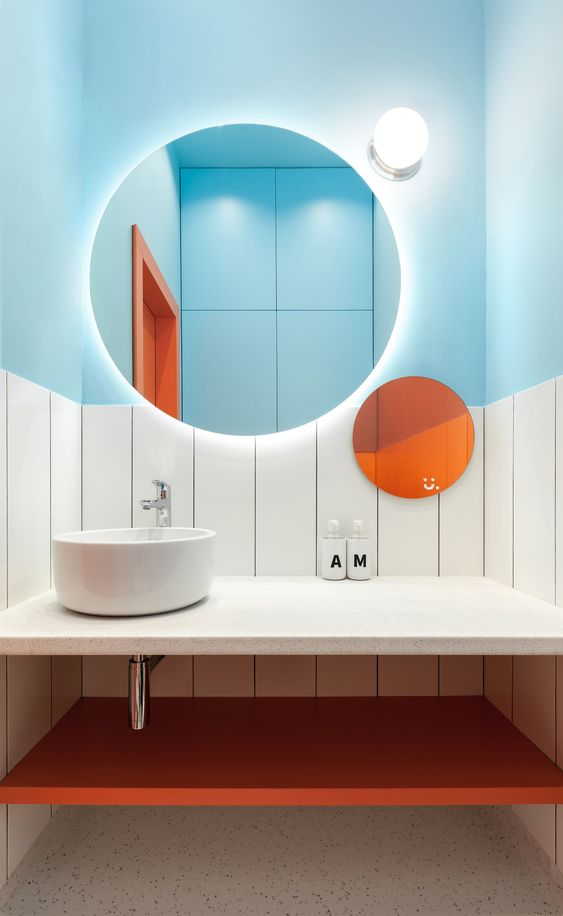 a bold bathroom with light blue half walls, an orange shelf and an orange round mirror for a bright look