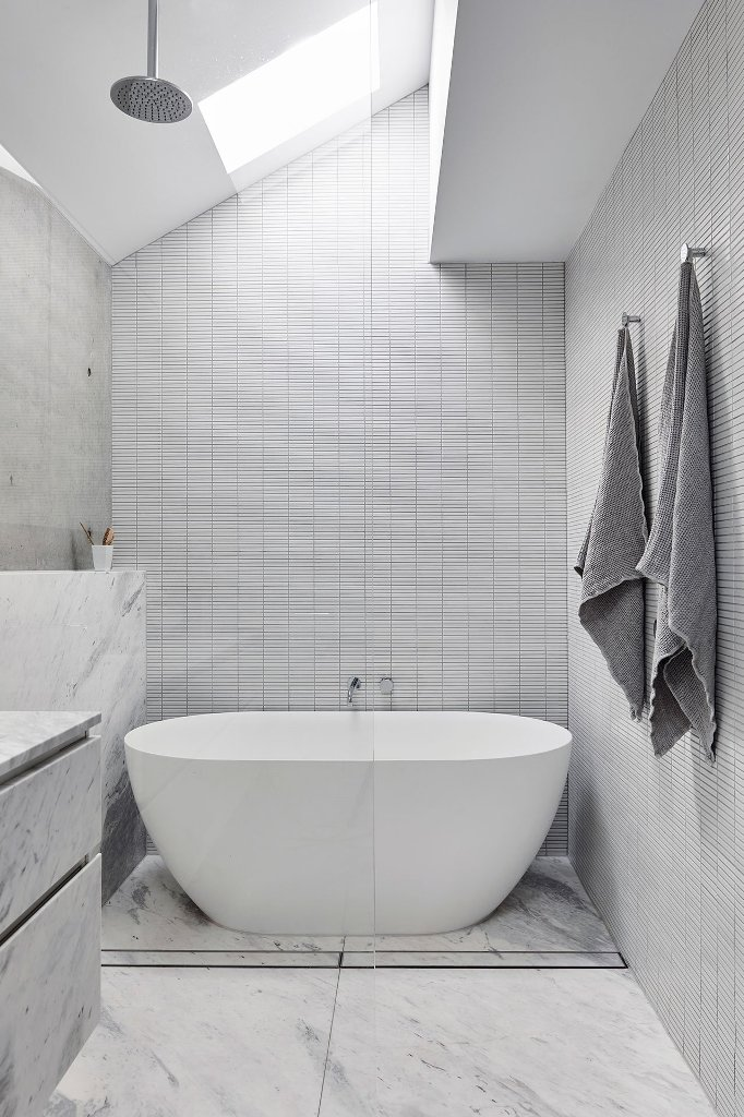 The bathroom features a skylight and a cool bathtub-shower space