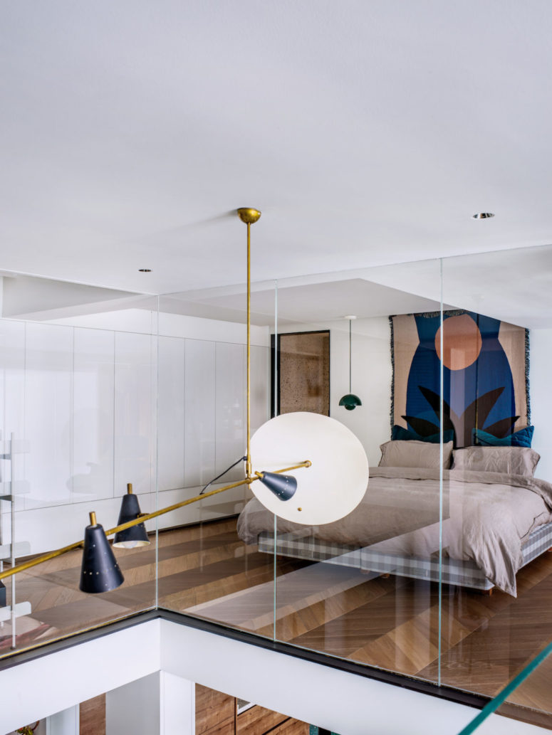 The bedroom features closed and sleek storage units, a floating bed, a bright artwork and hanging lamps