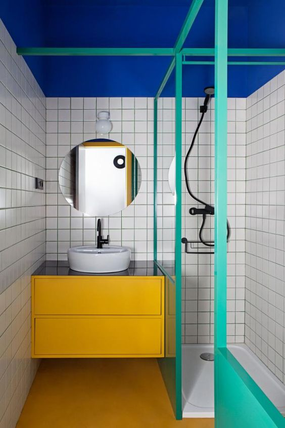 a bold modern bathroom with a bold blue ceiling, a yellow vanity and turquoise frames and half walls