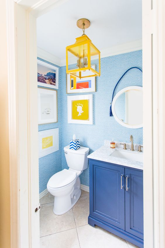 a bold powder room with blue penny tiles, a blue vanity, a yellow lantern and a pretty and bright gallery wall