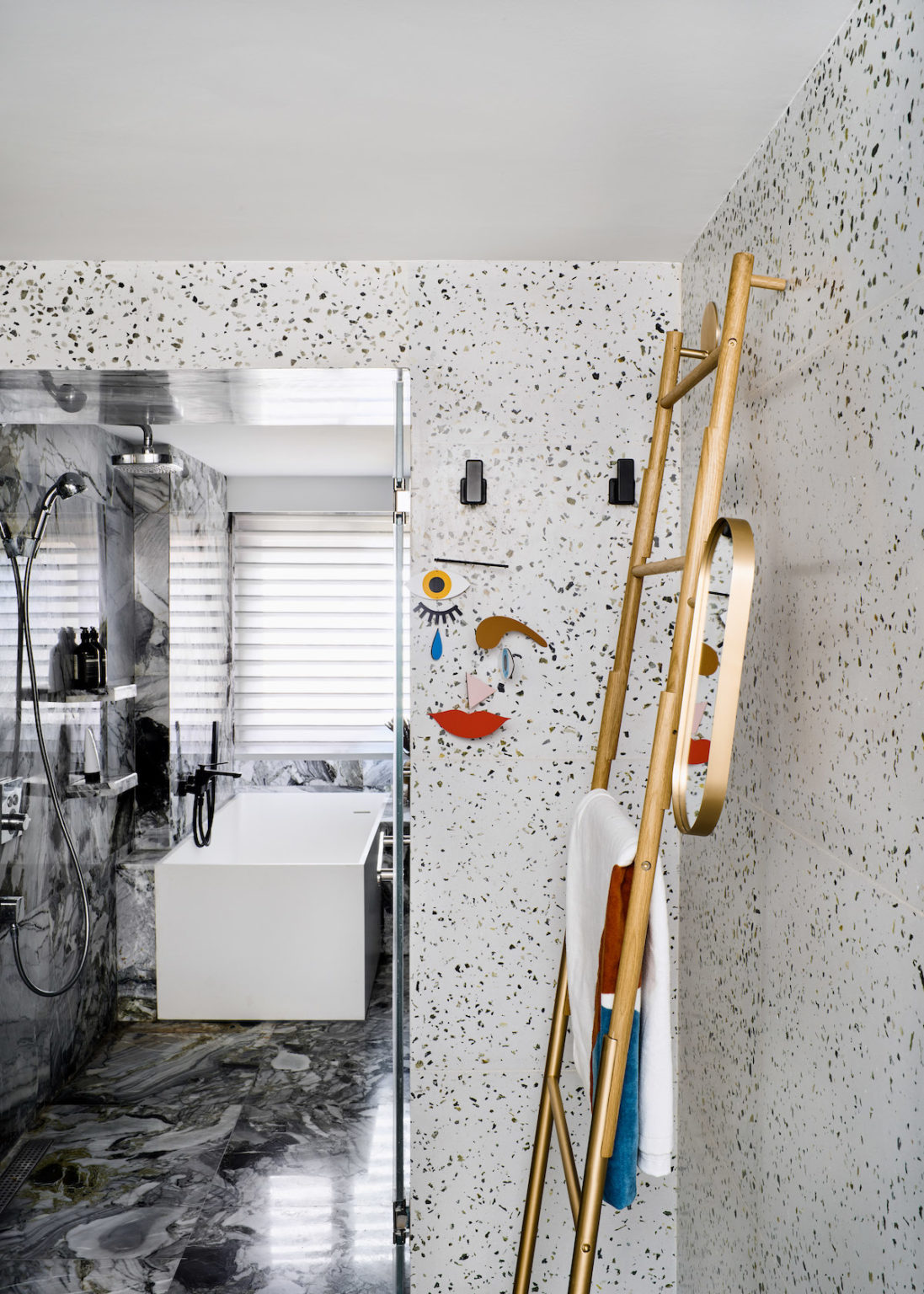The master bathroom is done with terrazzo and grey marble tiles, with modern fixtures and touches of gold