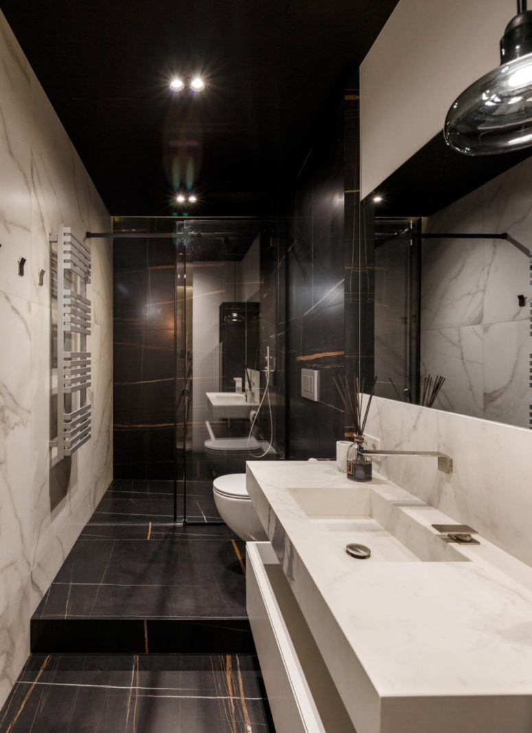 The second bathroom is clad with black marble and features a white marble sink and vanity in one