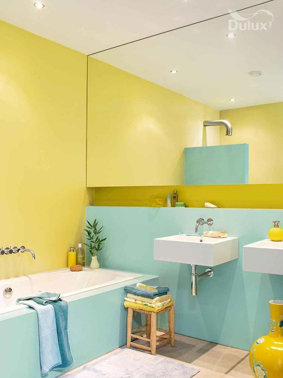 a bright color block bathroom in turquoise and yellow, with a large mirror, blue towels and sunny yellow touches